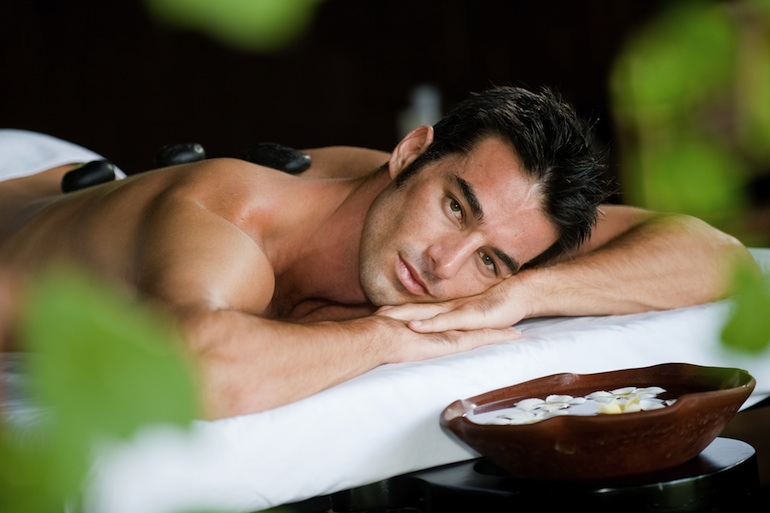 A good-looking man relaxing with hot stones on back before massage